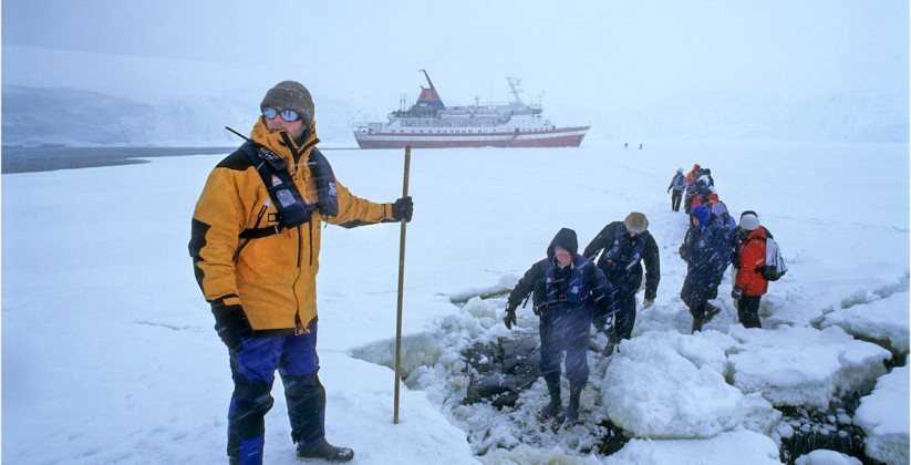 Tourists being guided during a snow storm over the ice with the expedition ship explorer parked in the ice on Antarctica