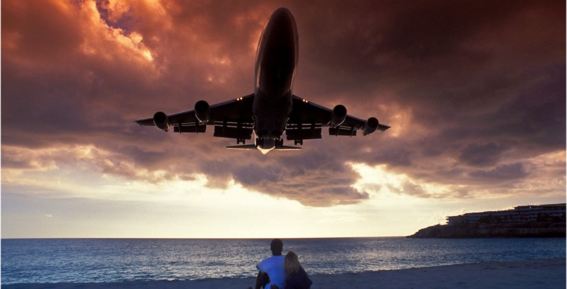 Airplane flying low over a beach on St. Maarten with two people scared