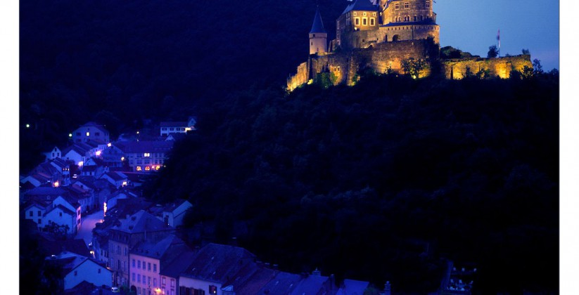 Vianden castle at night on a hill with the town of Vianden beneath it in Luxembourg